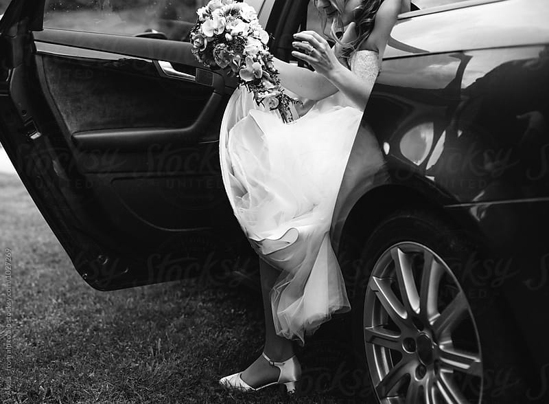 bride in white wedding dress getting out of a car in black and white by Leander Nardin for Stocksy United