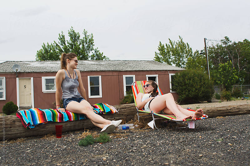 teenagers sunbathing in parking lot by Tana Teel for Stocksy United