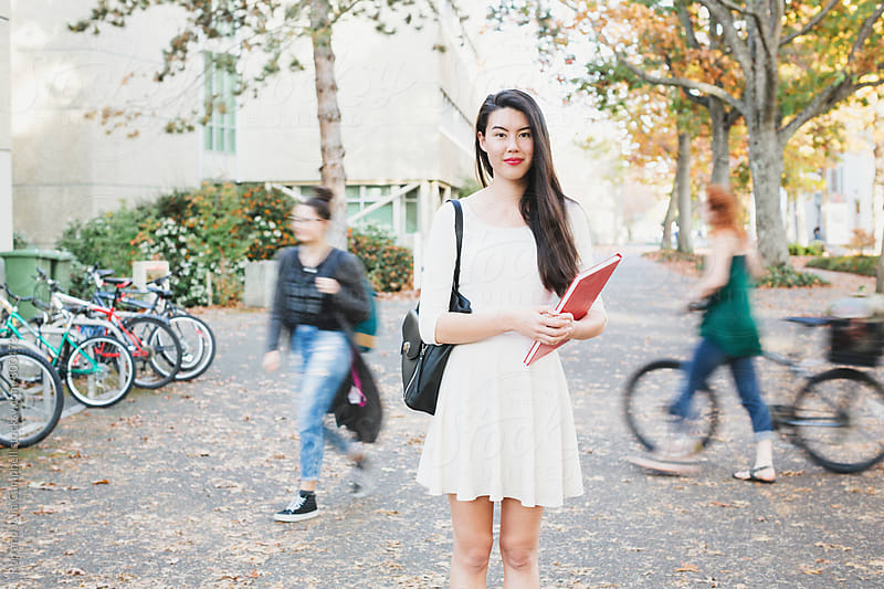Young mixed race woman standing on campus with blurry people in background by Rob and Julia Campbell for Stocksy United
