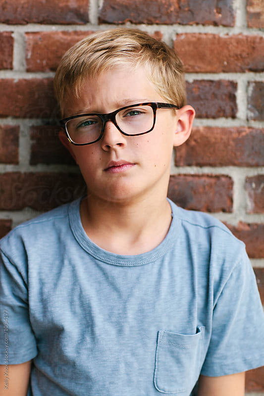 portrait of a serious boy in glasses by Kelly Knox for Stocksy United
