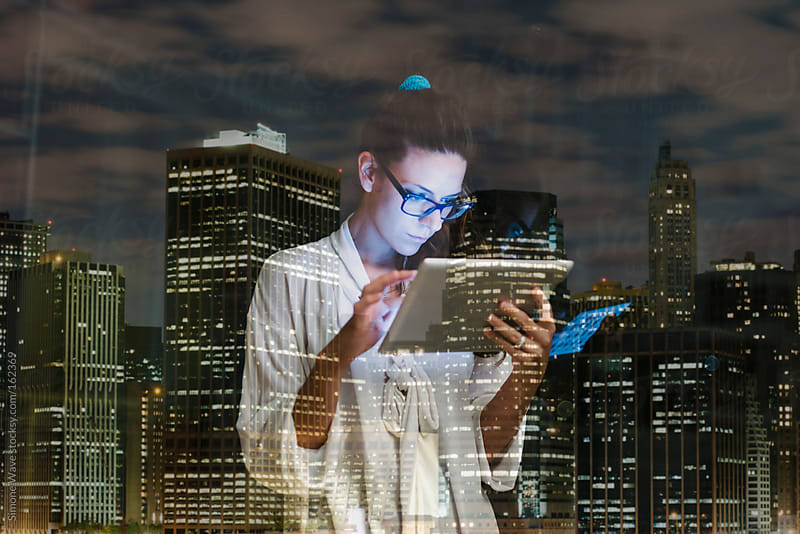 Young woman using digital tablet at home against city lights by GIC for Stocksy United
