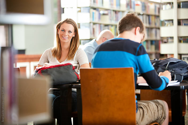 Library: Cheerful Teen with Friend, Doing Homework by Sean Locke for Stocksy United
