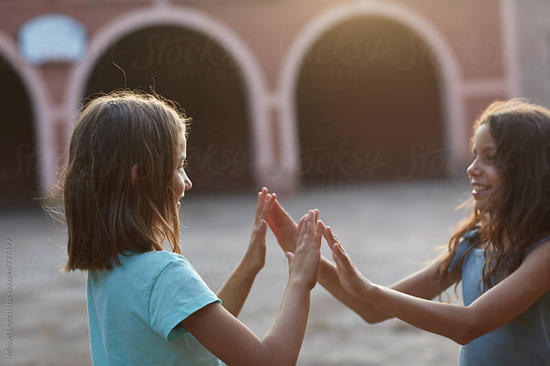 Two young girls playing a happy hands game by Miquel Llonch for Stocksy United