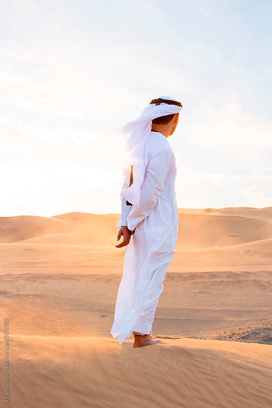 Arabian man wearing traditional costume in desert. Dubai. U.A.E by Hugh Sitton for Stocksy United