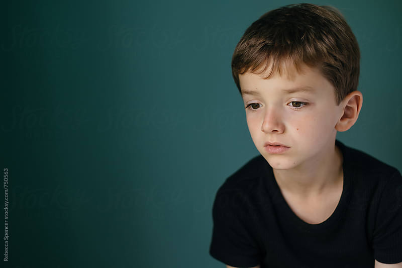 Boy in black top against a green wall by Rebecca Spencer for Stocksy United