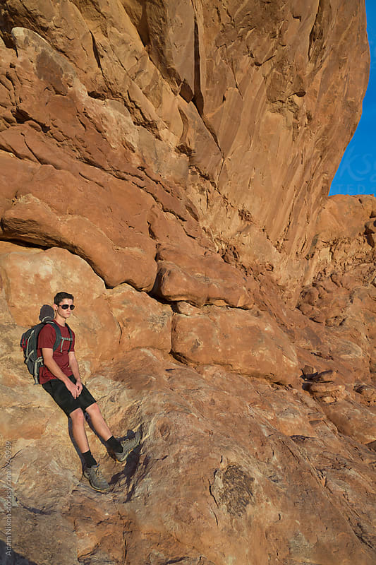 A hiker resting on sandstone red rocks by Adam Nixon for Stocksy United