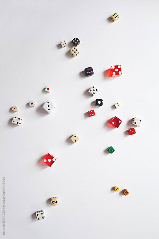 a collection of vintage dice scattered on a white background by Natalie JEFFCOTT for Stocksy United