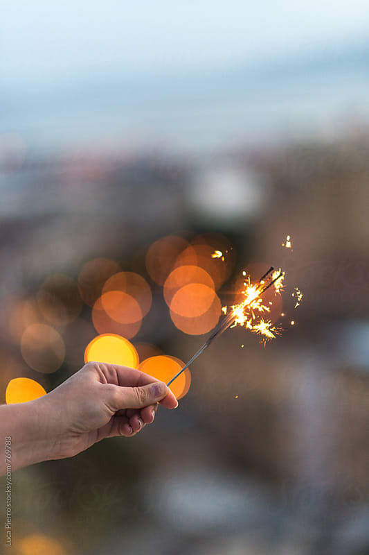 Woman's hand holding a sparkler by Luca Pierro for Stocksy United