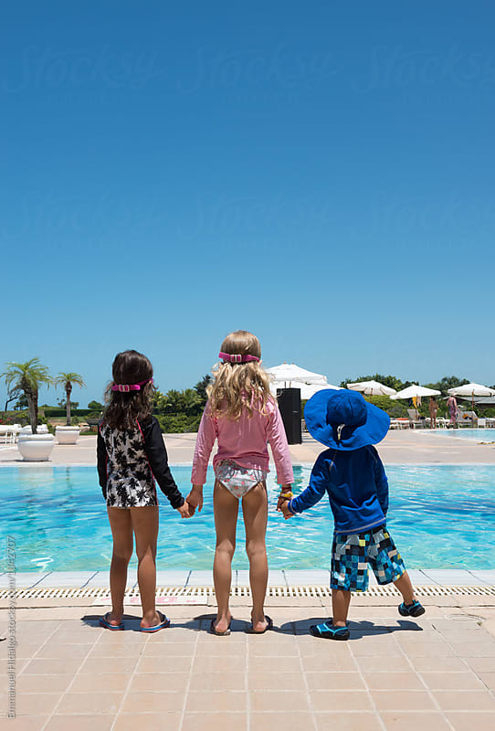 Young kids waiting poolside, holding hands by Emmanuel Hidalgo for Stocksy United