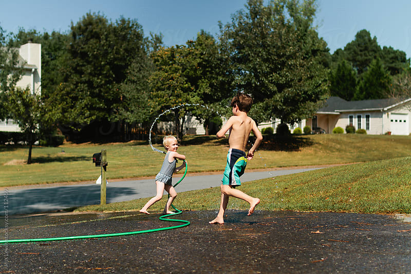 children playing with water hose by Jess Lewis for Stocksy United