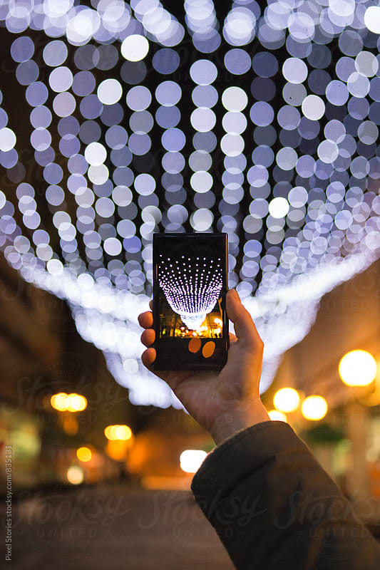 Woman taking photo of Christmas decoration by Pixel Stories for Stocksy United