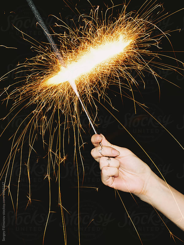 Crop hand holding bright sparkler  by Sergey Filimonov for Stocksy United
