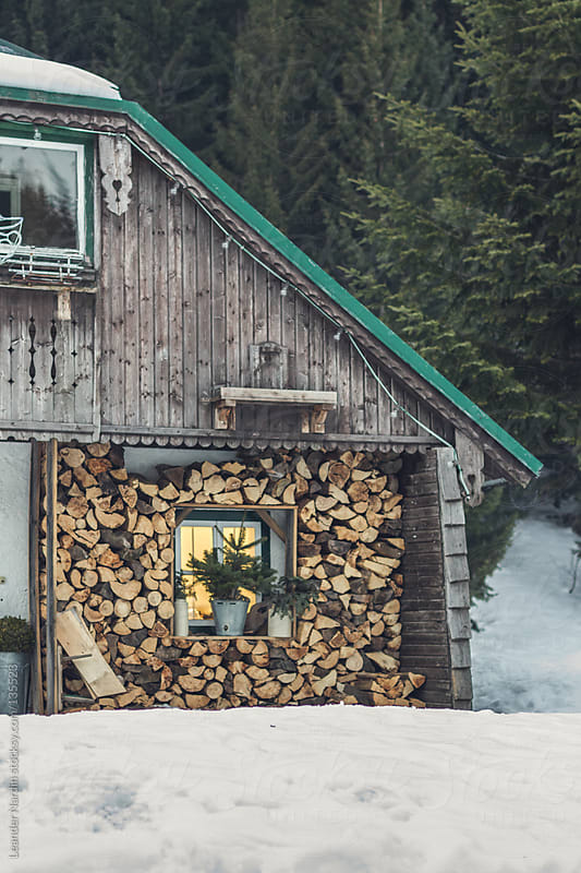 stack of logs below a rustic wooden roof by Leander Nardin for Stocksy United