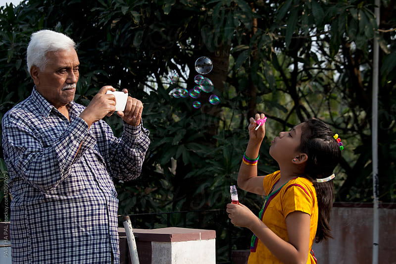 Active senior taking photo of his grandchild with smartphone by PARTHA PAL for Stocksy United