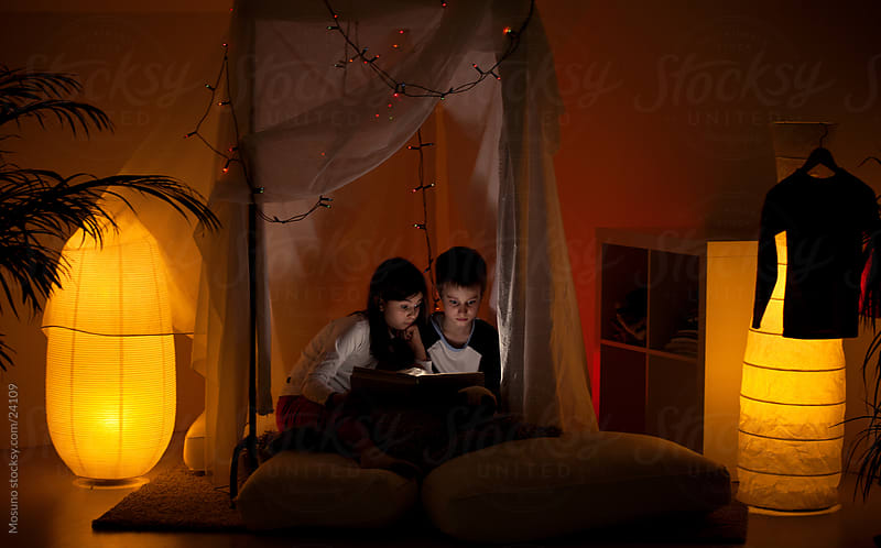 Brother and sister reading before sleep. by Mosuno for Stocksy United