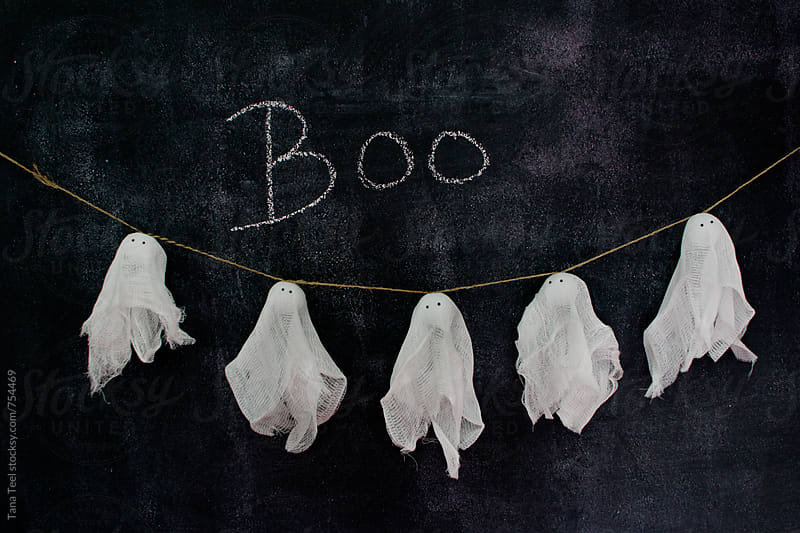 boo written on chalkboard above diy ghost garland by Tana Teel for Stocksy United