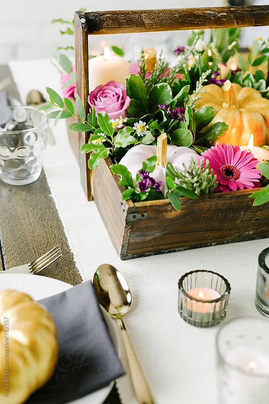 Pumpkin with candles and flower for table setting by Kirsty Begg for Stocksy United