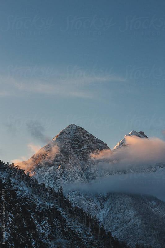 snowcovered mountain peak at sunrise by Leander Nardin for Stocksy United