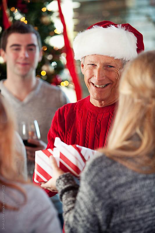 Christmas: Senior Man Handing Out Christmas Presents by Sean Locke for Stocksy United