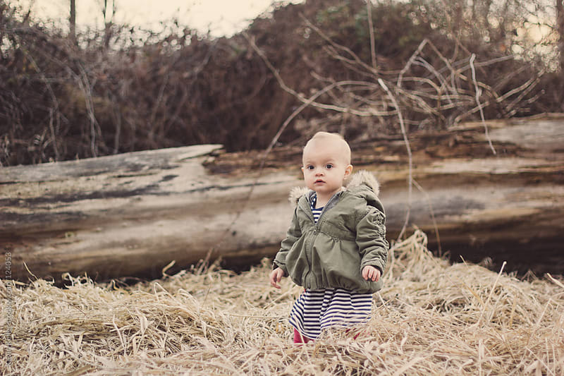 Toddler Girl standing in Dead Grass by Kevin Keller for Stocksy United
