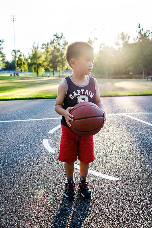 Asian kid holding a basketball in an outdoor basketball court by Suprijono Suharjoto for Stocksy United