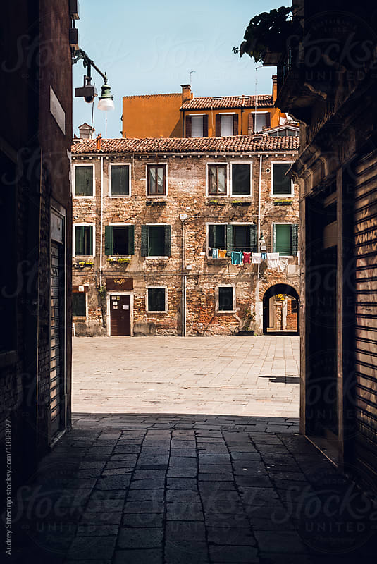 Look from dar alley on square and mediterranean style residences on square during sunny day.Italy by Marko Milanovic for Stocksy United