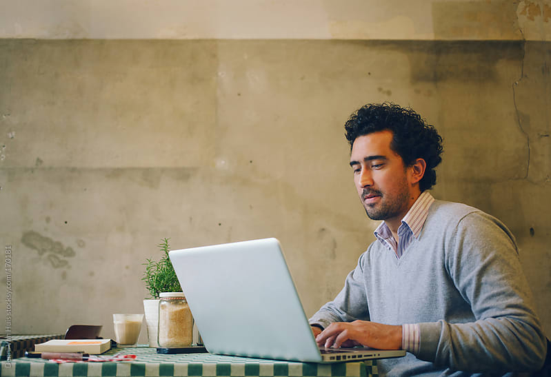 Young man working in cafe on a laptop  by Denni Van Huis for Stocksy United