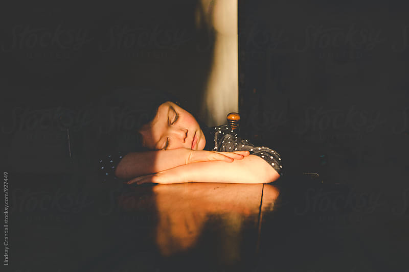 Young child resting insunlight by Lindsay Crandall for Stocksy United