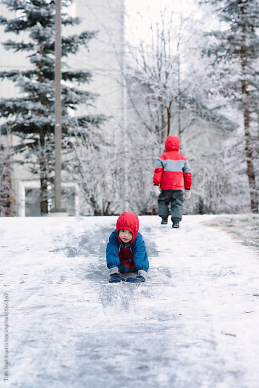 boys sliding without a sled - winter fun by Tara Romasanta for Stocksy United