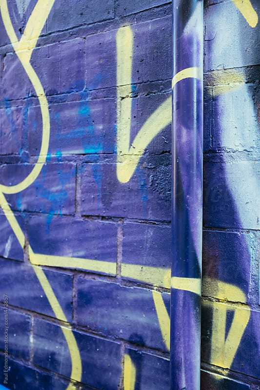 Graffiti covered wall and gutter pipe by Paul Edmondson for Stocksy United