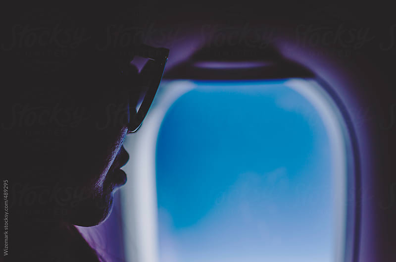 Young woman with sunglasses looking through an airplane window by Wizemark for Stocksy United