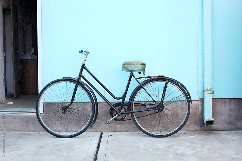 Old bicycle in front of a blue wall by Marija Mandic for Stocksy United