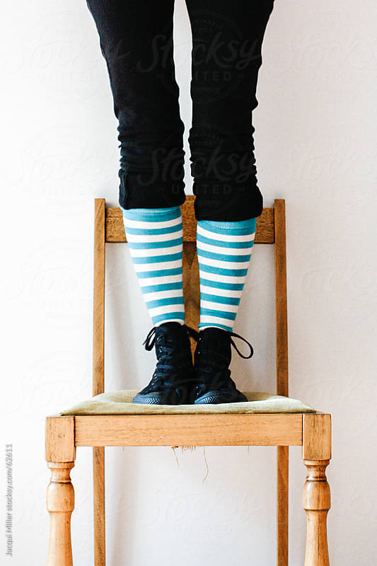Woman standing on an antique chair by Jacqui Miller for Stocksy United