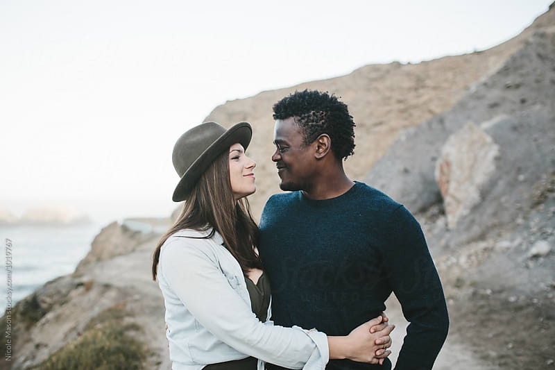 couple together on path in front of rocky landscape by Nicole Mason for Stocksy United