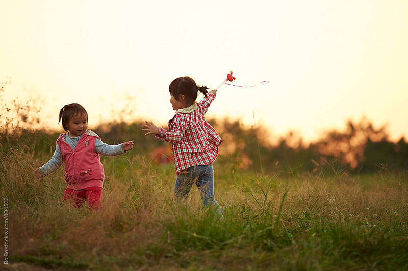 two happy asian little girl playing outdoor in the countryside by cuiyan Liu for Stocksy United