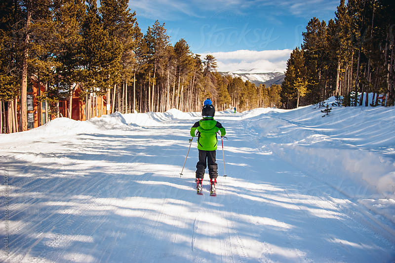 Boy skiing home down a snow covered road by Angela Lumsden for Stocksy United
