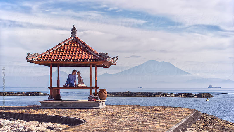 Young Couple sitting in traditional pagoda arbor at the beach  by Alexander Grabchilev for Stocksy United