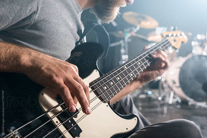 Closeup of hands playing electric bass guitar  by RG&B Images for Stocksy United