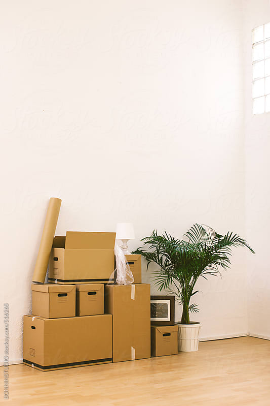 Stack of cardboard boxes in the new home.  by BONNINSTUDIO for Stocksy United
