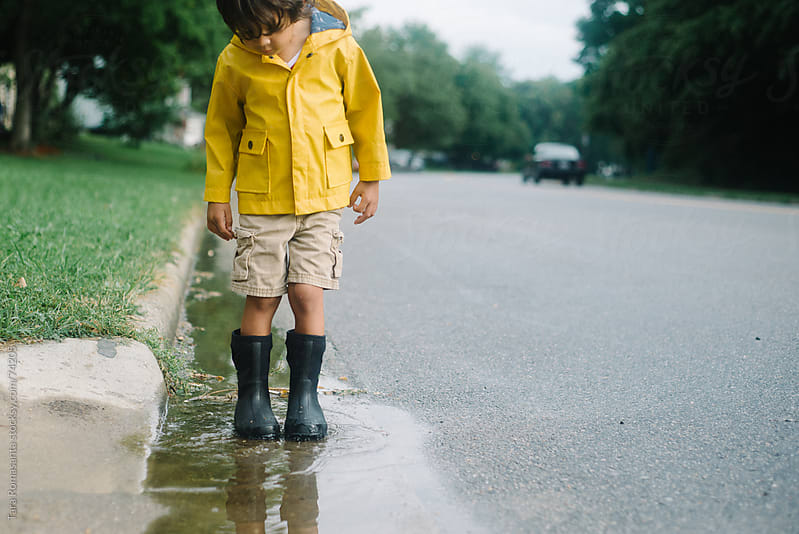 boy in rain jacket stands in a puddle by Tara Romasanta for Stocksy United