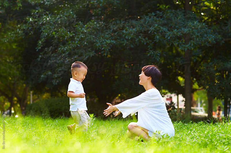 happy little asian boy with her mother outdoor in the summer park by cuiyan Liu for Stocksy United