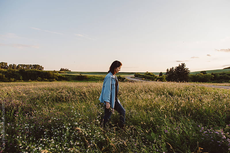 Woman walking through field of tall grass by Carey Shaw for Stocksy United