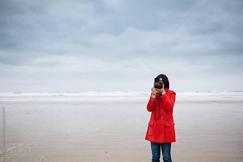 Woman taking a picture with a vintage camera at the beach by Suzi Marshall for Stocksy United