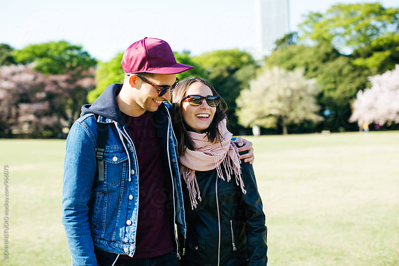 Young couple in love walking in a park. by BONNINSTUDIO for Stocksy United