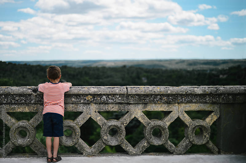 Caucasian boy  looking out over view in France. by Kirstin Mckee for Stocksy United