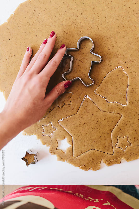 Woman shaping christmas cookies with cutters by Aleksandar Novoselski for Stocksy United