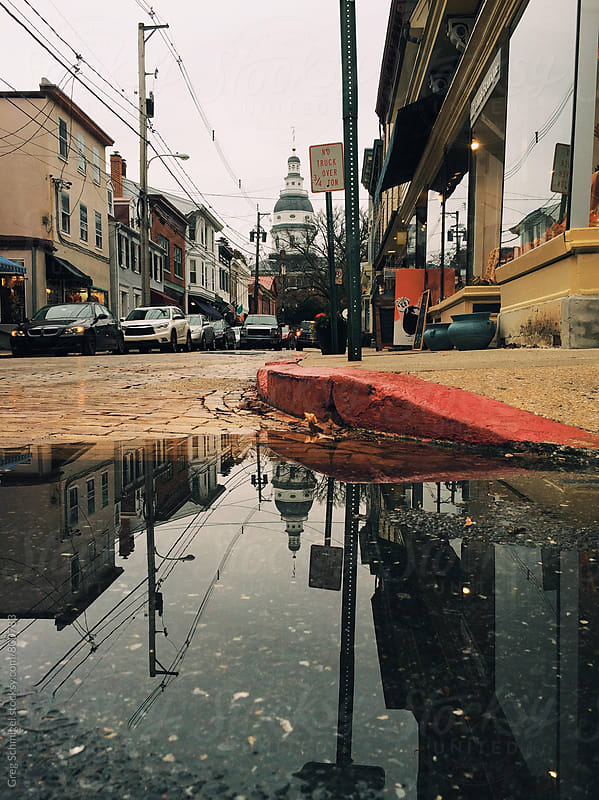 A small town street with a reflection of a domed building in a rain puddle on the street by Greg Schmigel for Stocksy United