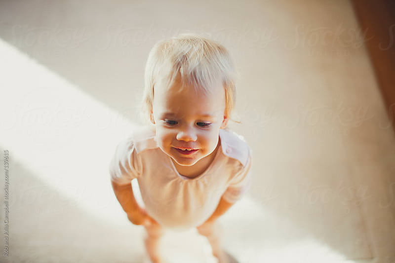 Cute toddler girl standing in ray of sunlight by Rob and Julia Campbell for Stocksy United