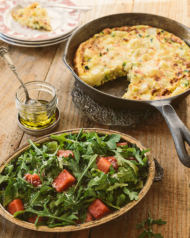 Close-up of arugula salad and potato frittata on frying pan by Trent Lanz for Stocksy United
