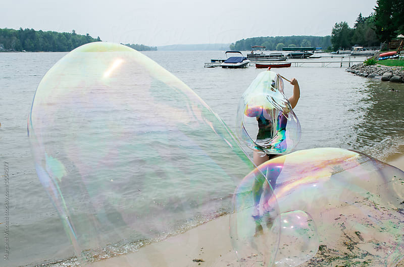 blowing giant bubbles by Margaret Vincent for Stocksy United